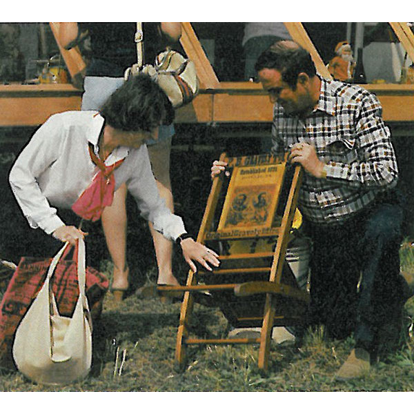 ralph and terry kovel at a flea market looking at a chair